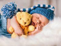 Baby newborn portrait, boy kid newborn sleeping in blue hat with teddy bear