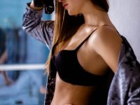 Portrait of beautiful lady in black lingerie and velvet robe standing with camera in hand